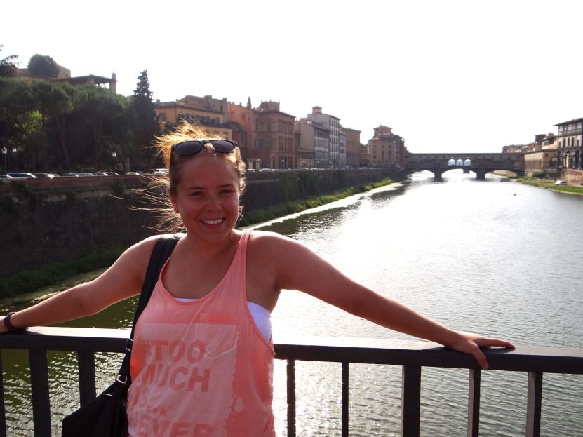 Brooke in Florence, Italy with the Ponte Vecchio Bridge in the background.